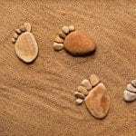 bigstock-trace-feet-steps-made-of-a-peb-546x546