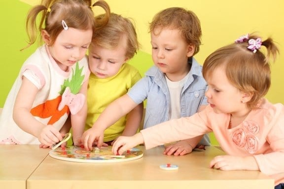 Two boys and two girls doing together wooden puzzle on the table