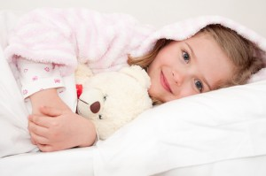 Cute girl in bed hugging no-name teddy bear