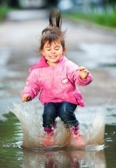 Girl jumps in puddle