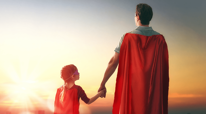 The backs of a little girl and a man, holding hands, both wearing superhero capes