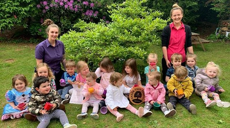 Gold award for Prenton nursery for eco-friendly thinking, 2 nursery workers and lots of little toddler children sitting on the grass smiling