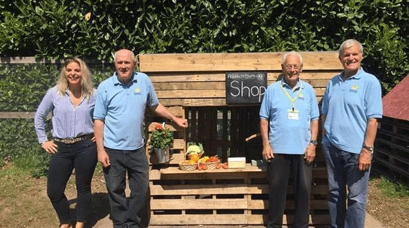 Romsey Men's Shed group build play shop for a local nursery, A woman and 3 older men stand outside the play shop they have built at Abbottswood day nursery