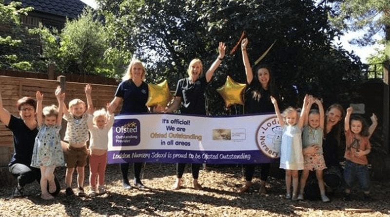 Excited group of nursery staff and toddlers pose with their arms in the air holding a sign stating that their nursery is 'outstanding'