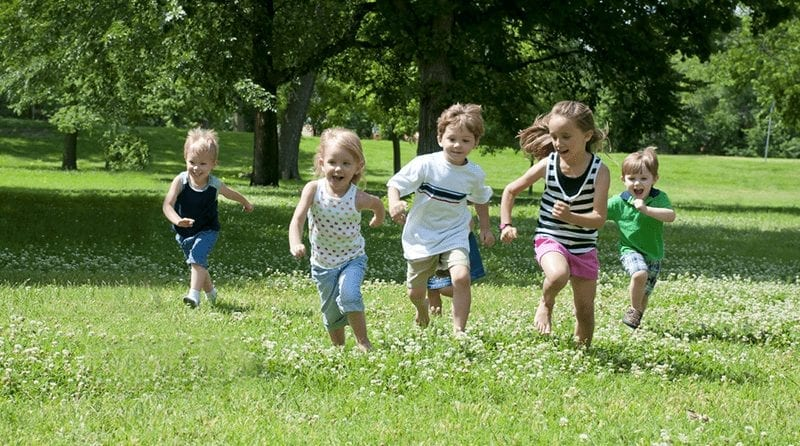Parents to spend over £500 in childcare costs over the summer, 5 little children running across the grass in a field on a sunny day