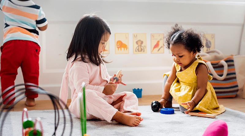 Two little girls sit on the floor playing with toys interacting with eachother