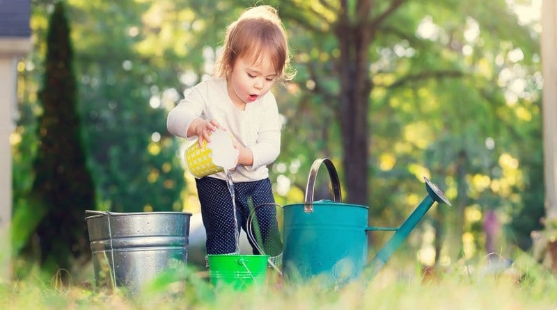 happy toddler girl playing with watering cans outside, Childminder Ofsted, Ofsted and Your Childminding Business