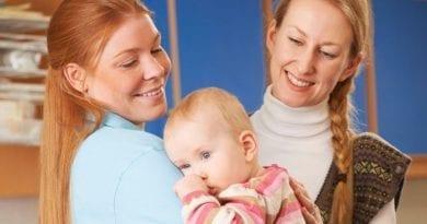 Nursery staff holding a baby