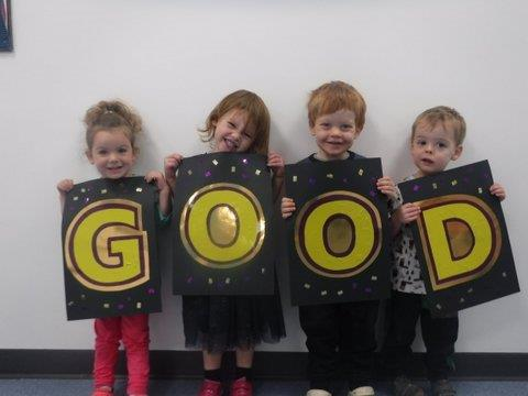 Boys and Girls Nursery children holding up a good sign
