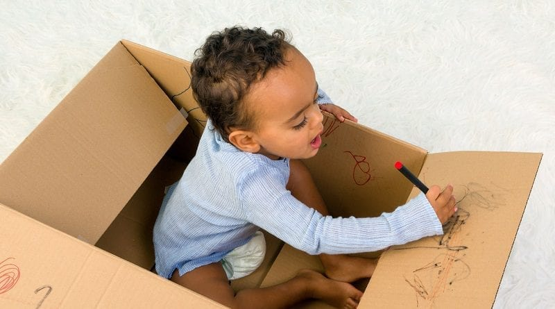 toddler boy sitting in a cardboard box playing with crayons