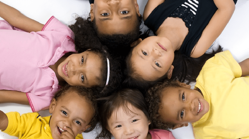 Group of children laying down forming a circle with their heads touching