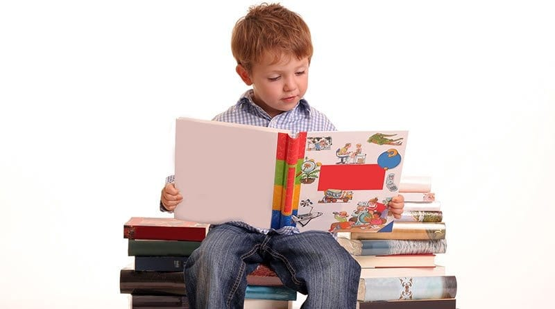 Boy reading a book whilst sitting on a pile of books, parenta magazine subscription