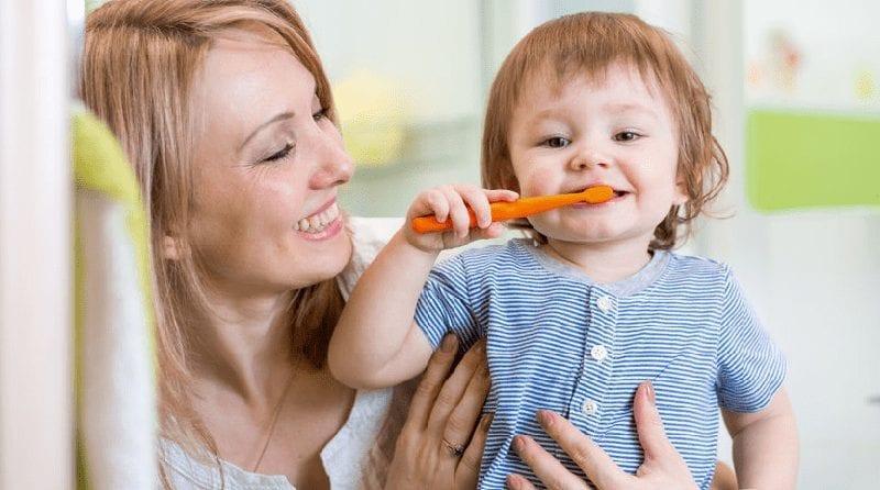 Toddler brushing teeth while mum looks over smiling