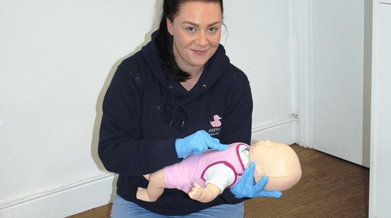 Woman performing first aid on a small doll
