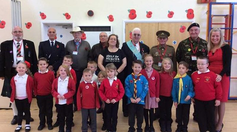Group of children and war veteran posing for a photo for Remembrance Day