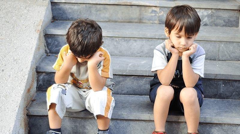 Two sad boys sitting on steps