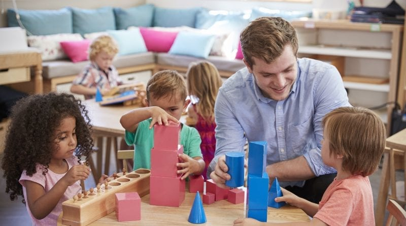 male nursery worker playing building blocks with children