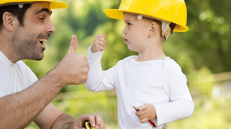 young boy and his dad giving thumbs up. Both are wearing yellow building helmets