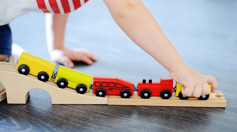 Close up of a child playing with wooden trains