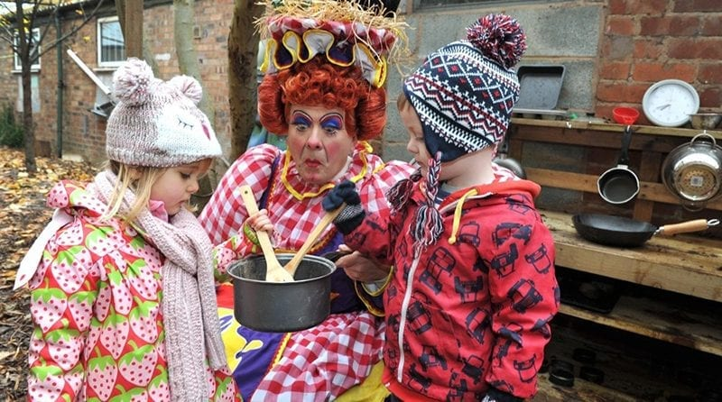 Pantomime character playing with children outside