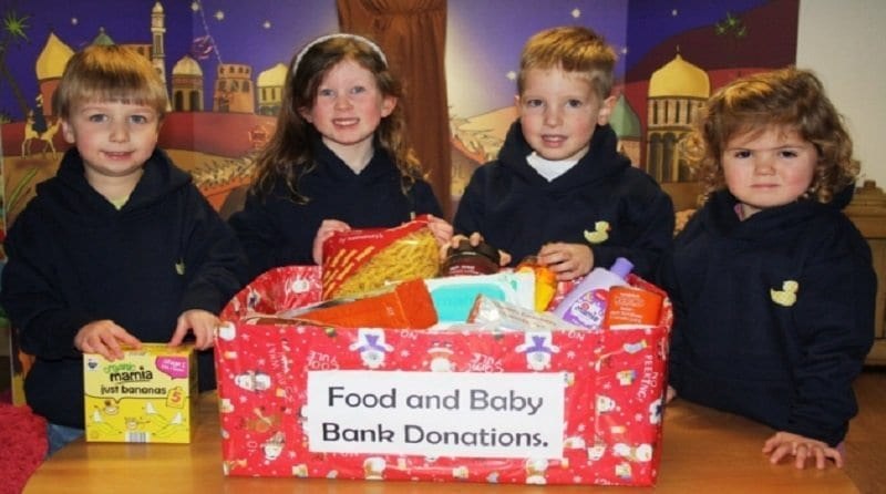 a group of nursery children are standing in front of a food bank donations box