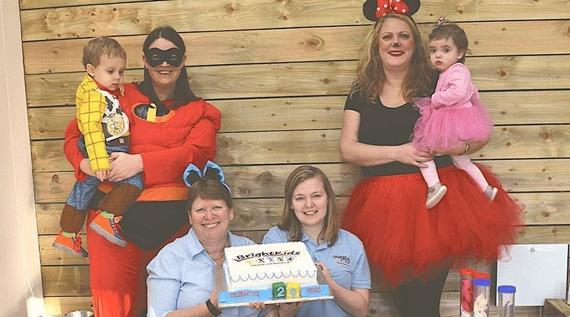 children and nursery staff dressed as Disney characters. Tow women are holding a cake