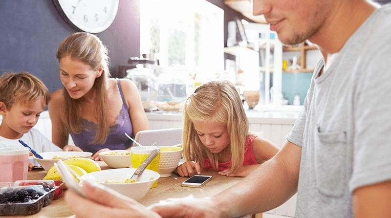 A family with tow children are sitting at the table all looking into smartphones