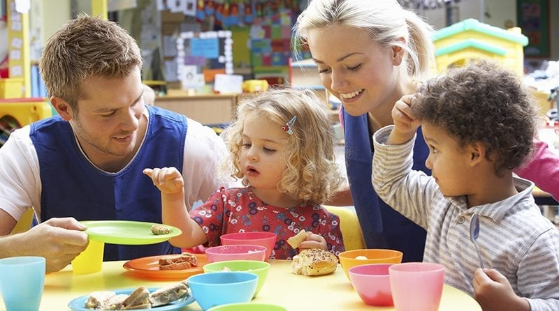 nursery staff and two children eating food at the table, Childcare Apprenticeships blog