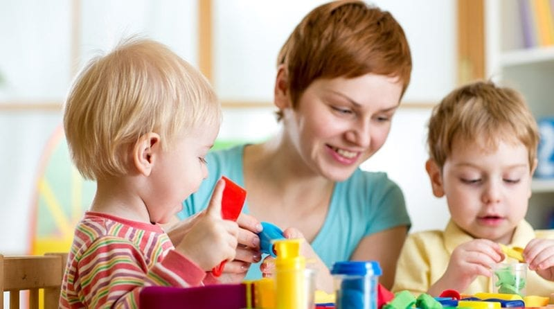 Nursery worker overlooking two toddlers playing at the table