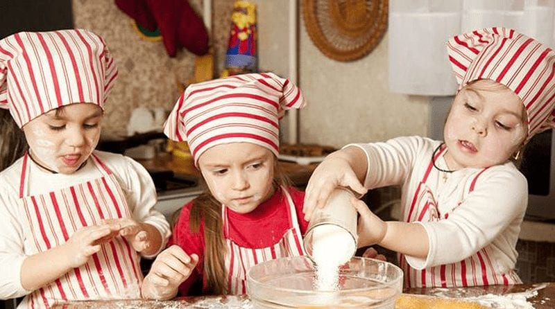 Three children dressed in baker outfits cooking