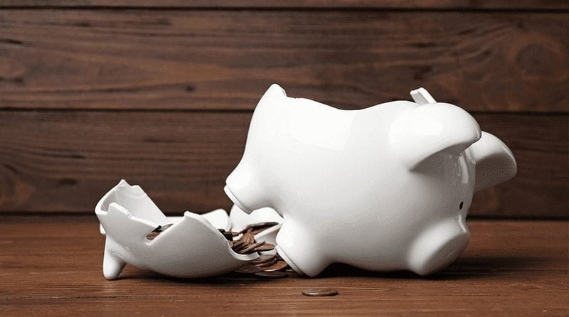 Broken white piggy bank on a wooden background, a small amount of coins showing
