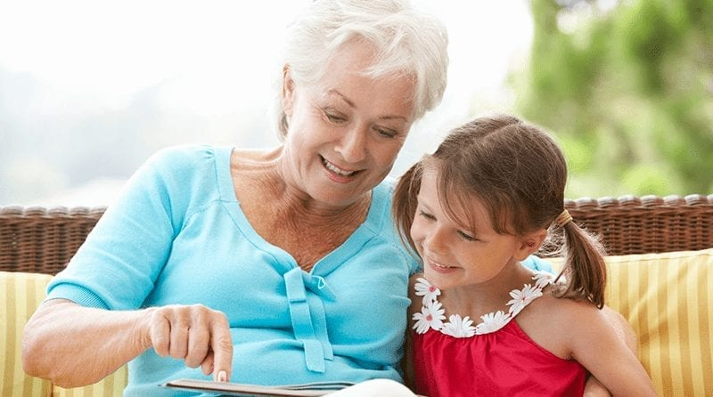 Little girl reading with her grandmother