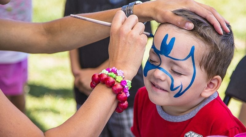 Little happy boy is having his face painted