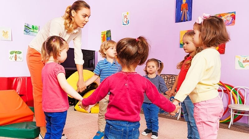 Group of nursery school children standing in a circle holding hands