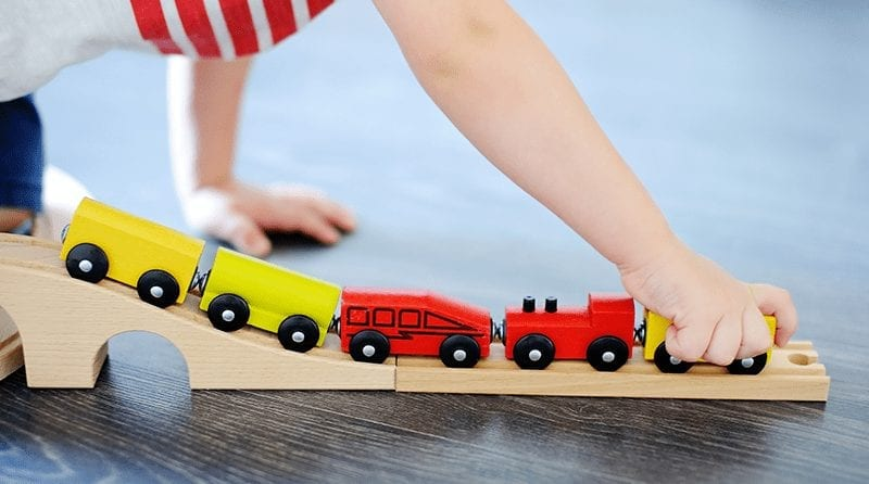 Little child plays with wooden toy train