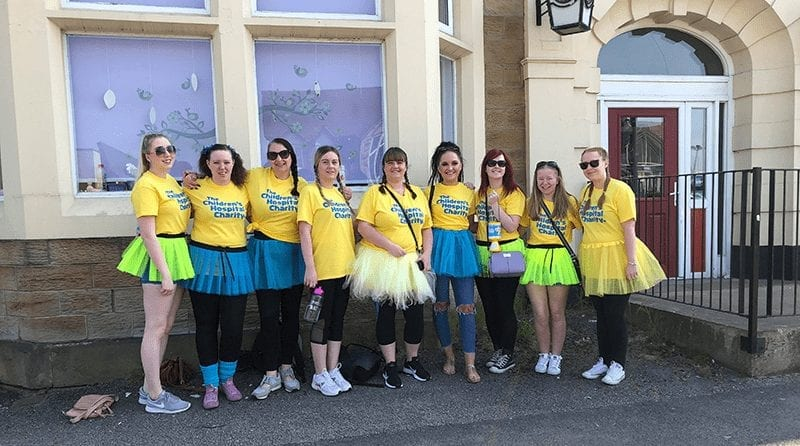 A group of your women dressed up in yellow tops and tutus standing outside of a building
