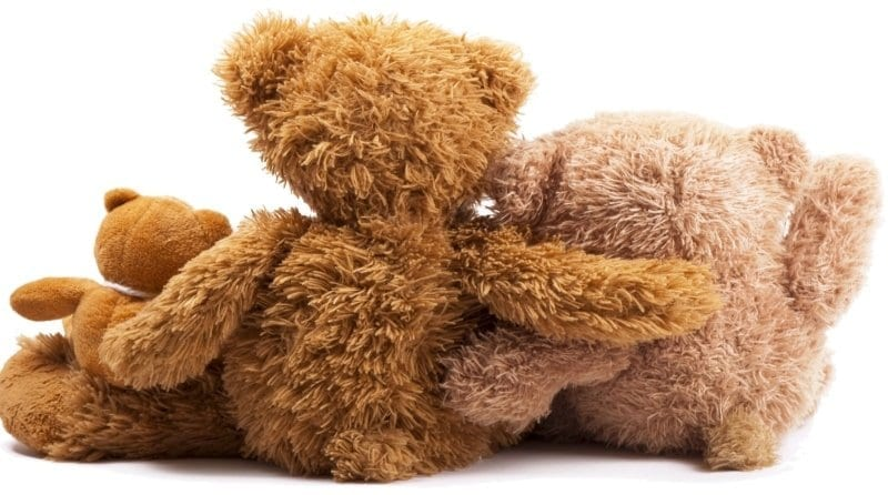 Three teddy bears holding each other. Back view