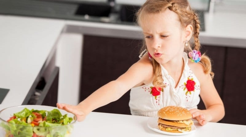 Little girl pushing away salad bowl but leaving the burger