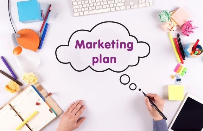 Marketing plan set up on a desk with a person holding a pen. Bird's-eye view.