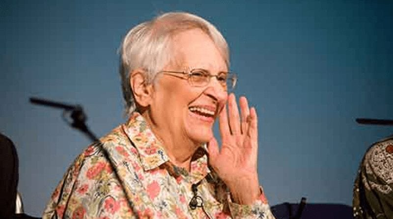 An older lady with glasses holding hand to her face smiling.