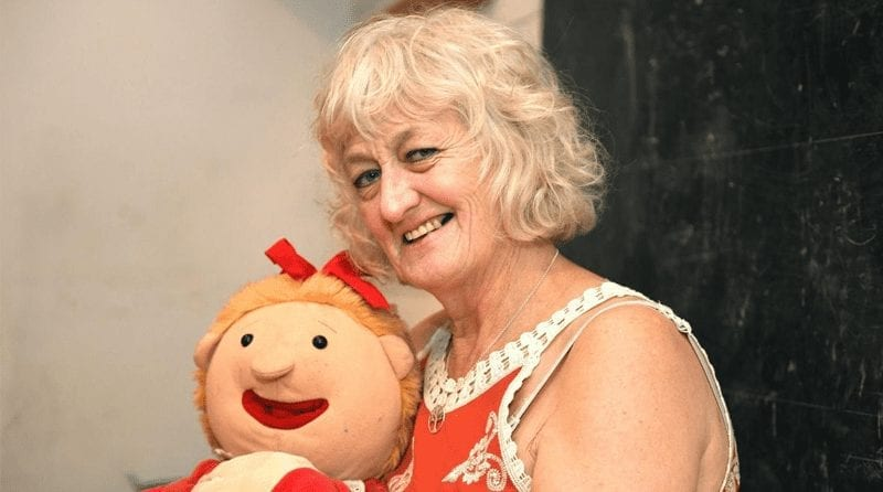 A woman holding a doll puppet