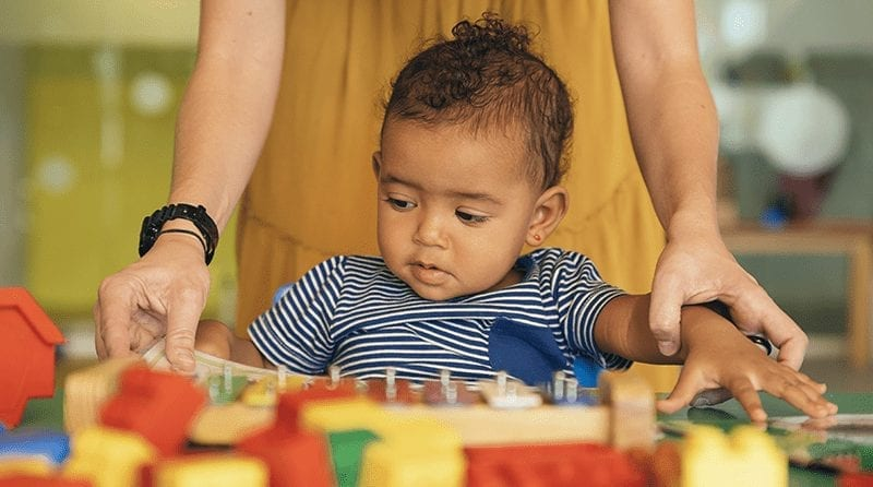 Toddler playing with toys whilst a person behind helps him