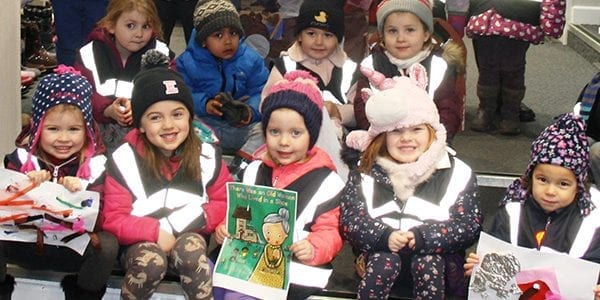 Children and nursery in winter outfits holding up posters