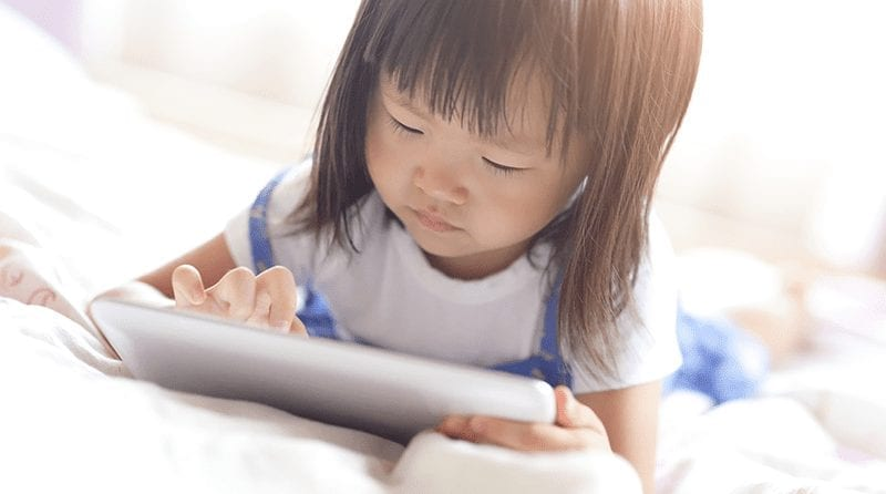 Little girl playing on a tablet. Blurred background