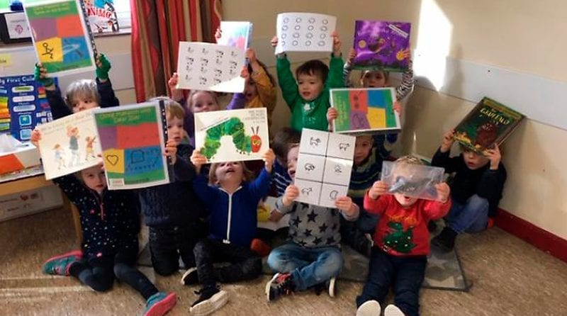 children at nursery holding up posters and books