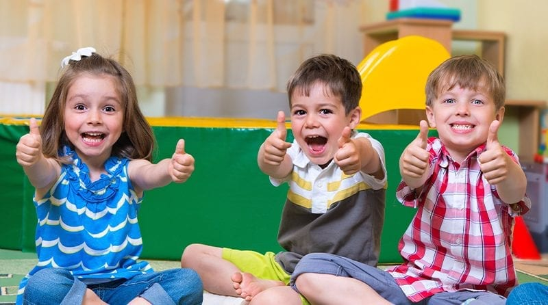 Three children giving thumbs up to the camera