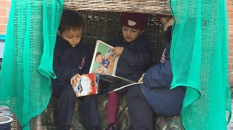 children in winter coats reading books outside