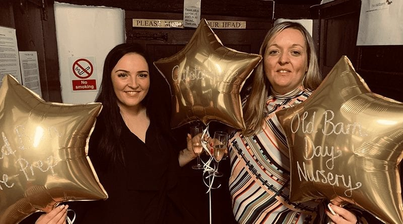 Two women holding gold star shaped balloons