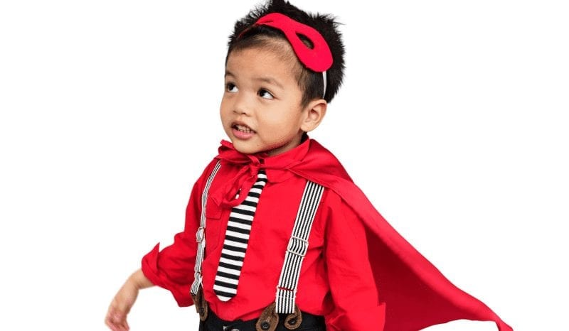 little boy dressed up as super hero. red superhero outfit