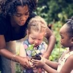 Teacher and two little girls are holding a plant in a vegetable garden